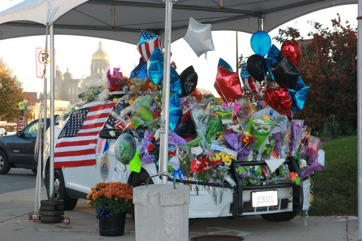 Central Iowans laid wreaths, flowers and memorabilia on a squad car, paying tribute to fallen officers Sgt. Tony Beminio and Officer Justin Martin, who were slain early Wednesday in ambush-style attacks. (Photo: Austin Hronich/The Simpsonian)