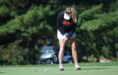Emily Jansen practices her swing at golf practice.