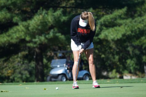 Emily Jansen practices her swing at golf practice.