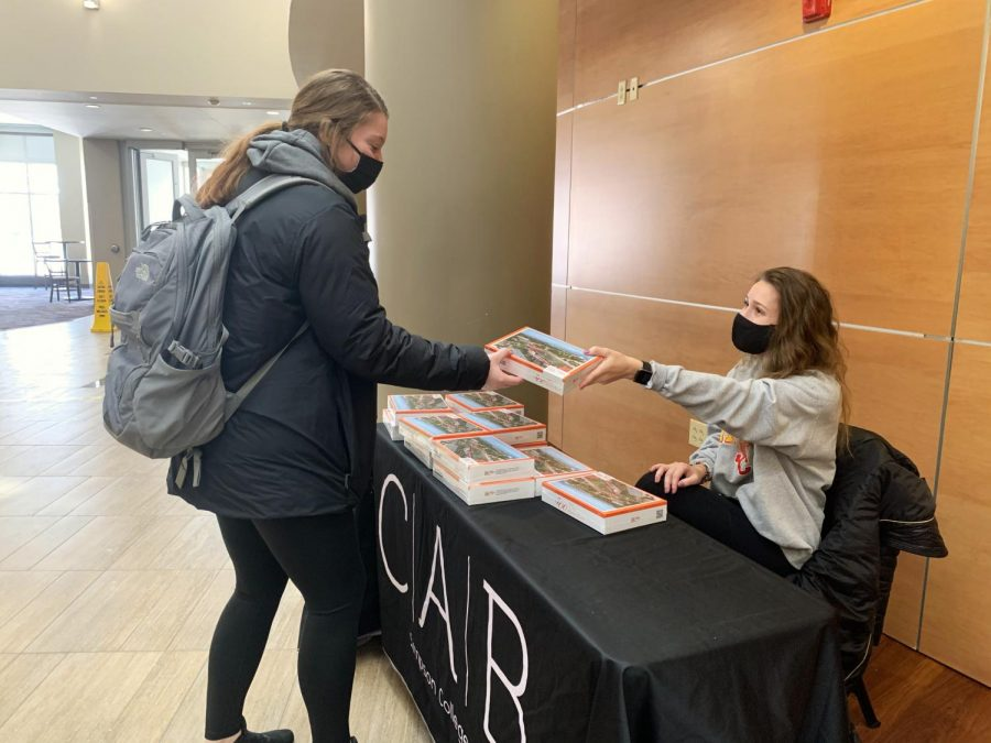 Simpson student picks up a free puzzle from CAB's weekly take & go.
