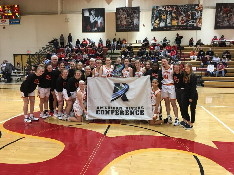 The Simpson Women's Basketball celebrates an American Rivers Conference Championship win after beating Coe 89-84. Photo by Zach Newcomer