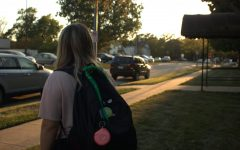 Many students' backpacks are adorned with green bandanas, signaling their support for suicide awareness.